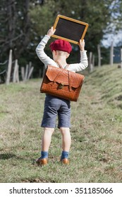 Young school boy in vintage clothing and red beret hat with leather school bag on his back hold up a small blackboard over his head (copy space)/School Boy and his Chalkboard