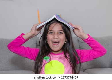 A young school girl covered her head with a book and she is happy