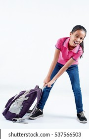 Young school girl dragging her heavy bag. Isolated in white background.