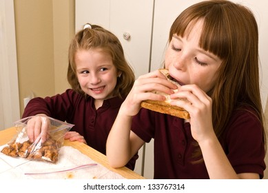 Young school girl eating lunch while a younger girls sneaks a pretzel