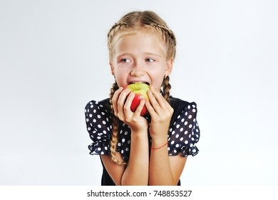 young school girl playing with fruits in a classroom