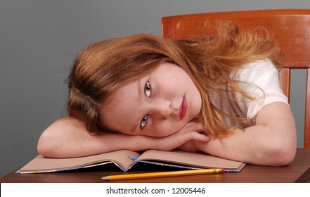 Young school girl putting head on desk, looking tired or bored