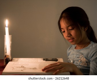 Young school girl reading a book by candle light.
