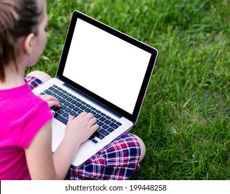 Young school girl wearing colorful outfit using the laptop on a grass field in the park. Back to school, lifestyle, technology young fashion concept