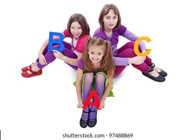 Young school girls holding letters of abc learning together