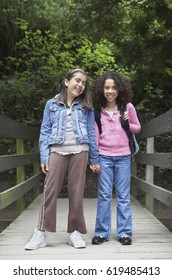 Young school girls posing on wooden bridge