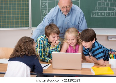 Young school kids in class grouped around a laptop computer on a desk with a male teacher leaning over watching them work