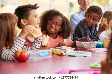 Young school kids eating lunch talking at a table together - Shutterstock ID 1177724494