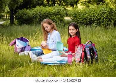 Young school kids eating lunch talking, together, sitting on the ground, outdoor