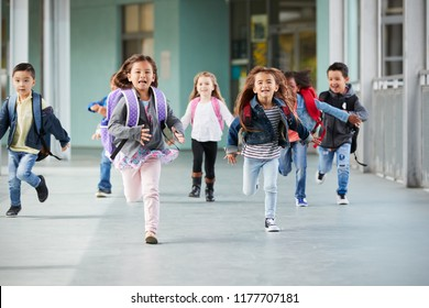 Young school kids running in a corridor in their school, close up