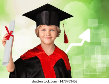 A young schoolboy in a graduate gown holds a diploma