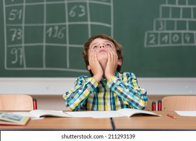 Young schoolboy searching for answers sitting at his desk in the classroom staring up into the air with a thoughtful expression