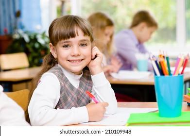 Young schoolgirl in classroom. looking at camera