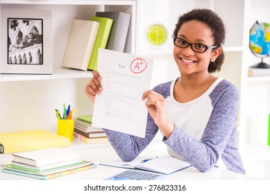 Young schoolgirl  in glasses sitting at the table and  showing perfect test results on colorful background.