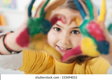 young schoolgirl hands forming a heart symbol, Selective Focus, Focus is on the Face