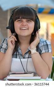 Young schoolgirl listening to music with big headphones