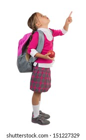 Young schoolgirl in pink school uniform and a backpack holding an apple and pointing with her finger towards something above her, isolated
