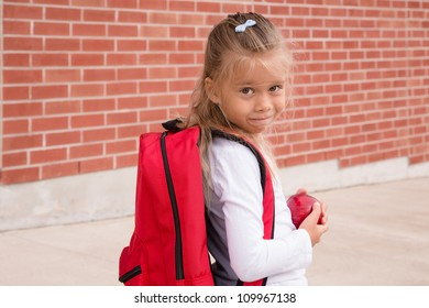 Young Schoolgirl with red backpack standing against brick school wall, holding an apple