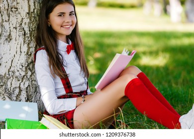 young schoolgirl in school uniform sitting on the grass under a tree with books.