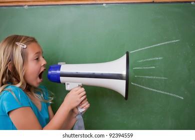 Young schoolgirl screaming through a megaphone in front of blackboard