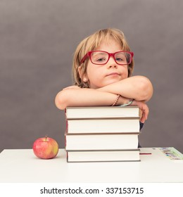 Young schoolgirl waring big red glasses leaning on a stack of thick books next to an apple