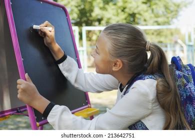 Young schoolgirl writing Back to school on blackboard, education concept