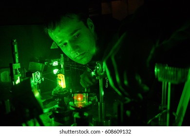 A young scientist customizes of laser systems for experiments in the laboratory.