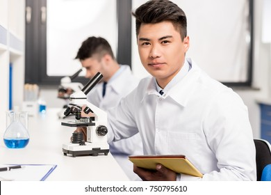 Young scientist in lab coat sitting at table in laboratory with microscope and digital tablet and looking at camera