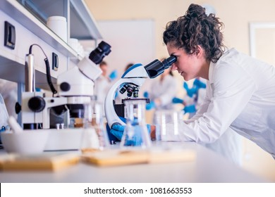 Young scientist looking through a microscope in a laboratory doing research