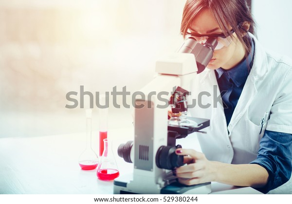 Young scientist looking through a microscope in a laboratory. Young scientist doing some research.