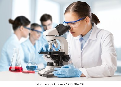 The young scientist team has researching in the laboratory with a microscope.