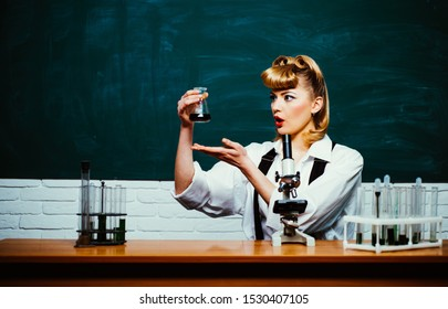 Young scientist works in modern biological lab. Learn about science in a natural classroom. Woman with test tubes. Research to save the environment.