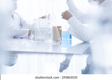Young scientists with pipette and flask making test or research in clinical laboratory