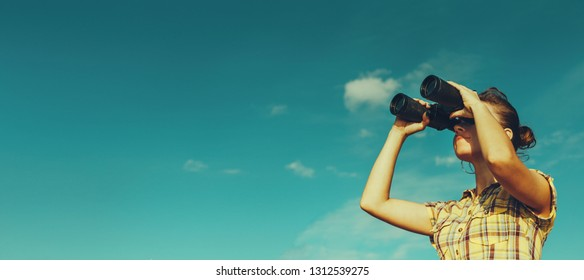 Young scout girl looks through binoculars on blue sky background