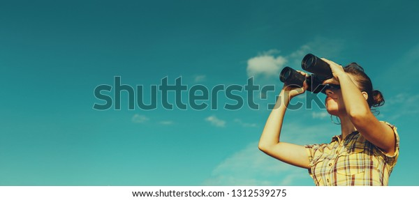 Joven scout mira a través de prismáticos sobre fondo azul del cielo