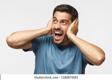 Young screaming angry man shout at noisy neighbours from the top; stressed by noise, closing ears with both hands