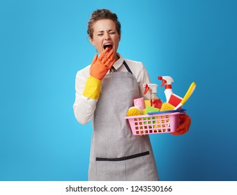 young scrubwoman in apron with a basket with cleansers and brushes yawning on blue background. Tired and exhausted professional woman cleaner after a busy day