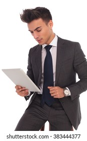 young seated business man reading on his tablet computer on white background