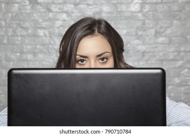 the young secretary hides behind the monitor