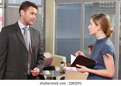 young secretary talking to her boss in the office