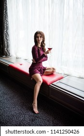 young seductive beautiful woman in a red dress sitting on a dark couch with a glass of red wine