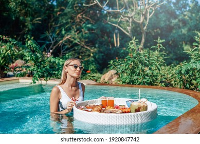 Young seductive woman eating asian food swims in a pool with floating table in modern and luxurious hotel.
