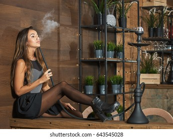 Young seductive woman smoking a hookah in a restaurant with a nice wooden design