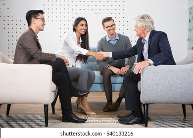 Young and Senior Business People Shaking Hands