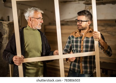Young and senior carpenter with a wooden frame