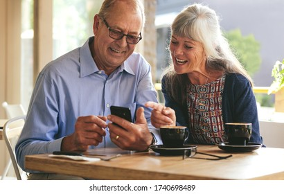 Young senior couple sitting at table in cafe and looking at mobile phone and smiling. Retired man and woman in coffee shop using smart phone.