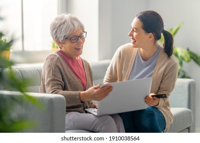 Young and senior women are using laptop pc. Daughter is helping mother having fun staying at home.