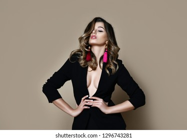Young sensual beautiful sexy woman posing in fashion black jacket suit naked on warm beige background