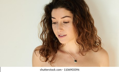 Young sensual brunette with curls and naked shoulders looking down on background of white wall