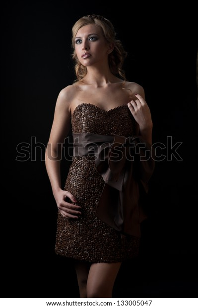 young sensual caucasian woman in dress made of coffee beans standing over gradient orange background